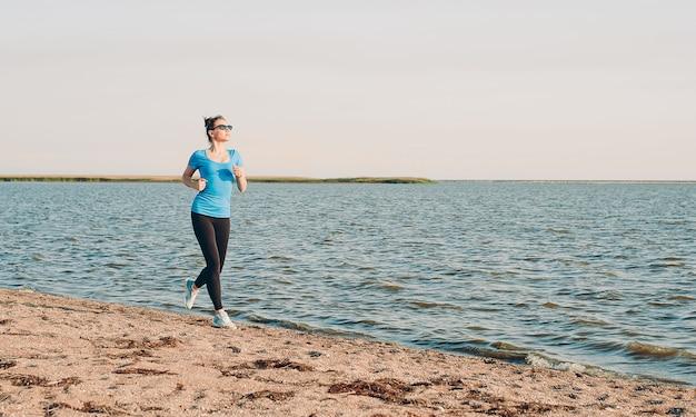 実行している若い女性。日当たりの良い夏の砂のビーチで実行されている女性ランナー。海海海岸近くのトレーニング。美しいフィットの女の子。フィットネスモデル白人民族屋外。減量運動。ジョギング。