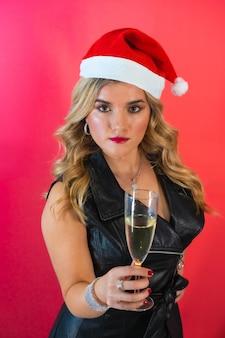 Giovane donna con un cappello da babbo natale e un elegante abito nero in posa con un bicchiere di champagne