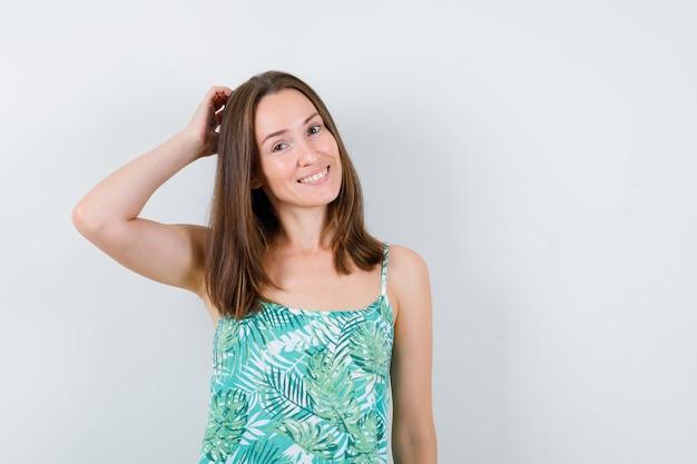 Giovane donna che si gratta la testa in camicetta e sembra allegra, vista frontale.