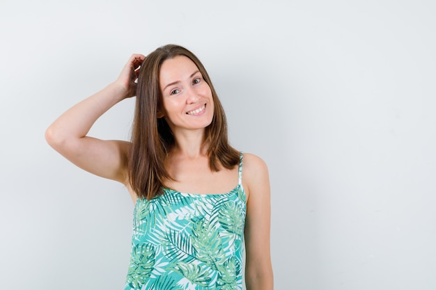 若い女性がブラウスで頭を掻いて陽気に見える、正面図。