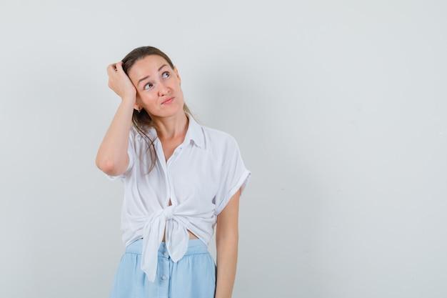 Девушка почесывает голову в блузке и юбке и выглядит нерешительно
