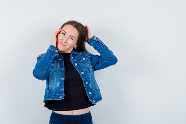 若い女性はブラウス、ジャケットで頭を掻き、忘れて見える、正面図。