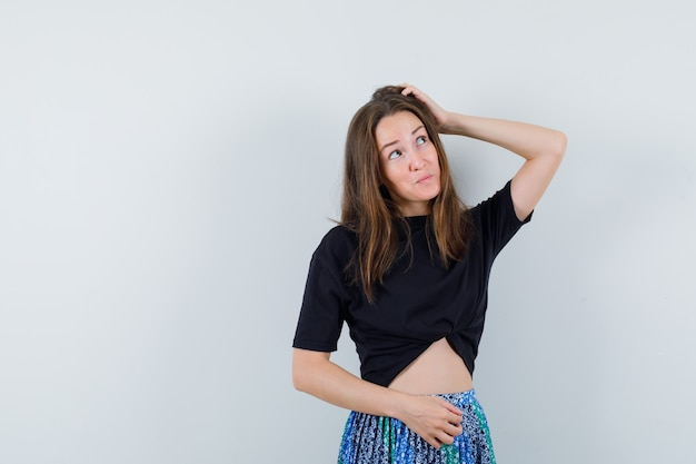 Девушка почесывает голову в блузке, юбке и задумчиво смотрит