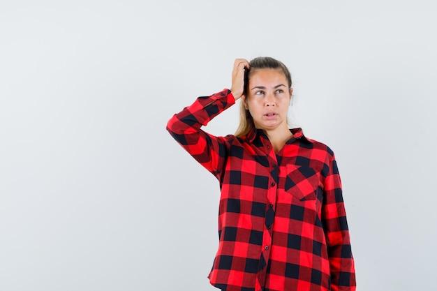 Молодая леди почесывает голову в клетчатой рубашке и выглядит забывчивой