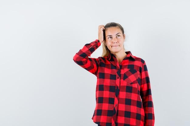 Молодая леди почесывает голову в клетчатой рубашке и выглядит нерешительно