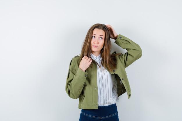 若い女性はシャツ、ジャケットで頭を掻き、優柔不断な正面図を探しています。