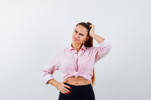 Девушка почесывает голову в рубашке, штанах и задумчиво. передний план.