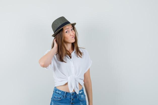 若い女性がtシャツ、ジーンズ、帽子で頭を掻き、思慮深く見える、正面図。