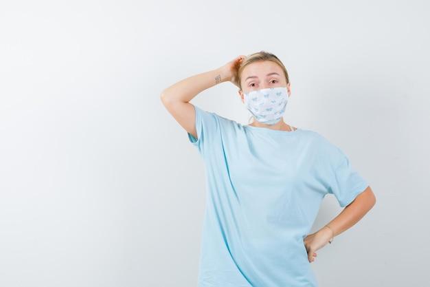 若い女性がtシャツ、マスクで頭を掻き、注意深く見て