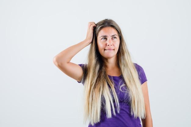 Giovane donna che graffia la testa in maglietta viola e sembra indeciso, vista frontale.