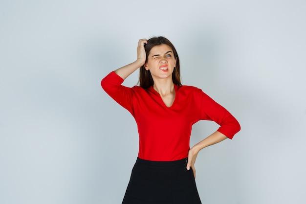 Giovane signora che graffia la testa mentre tiene la mano sull'anca in camicetta rossa