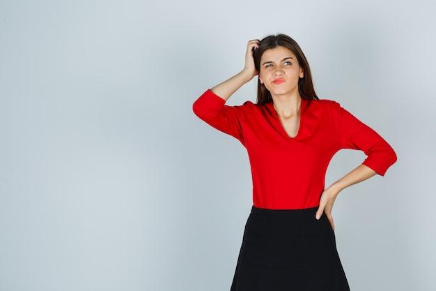 赤いブラウスで腰に手を保ちながら頭を掻く若い女性