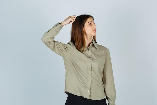 Giovane donna che si gratta la testa mentre guarda da parte in camicia, gonna e sembra concentrata. vista frontale.