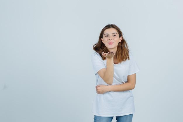 Tシャツ、ジーンズ、キュートに見える、正面図で手でキスを送信する若い女性。 無料写真