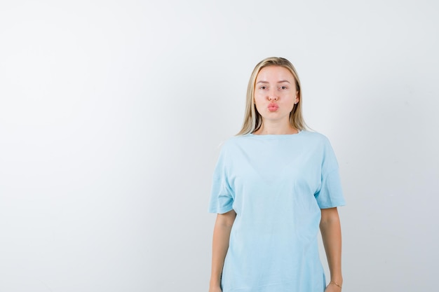 Young lady sending kiss with pouting lips in t-shirt and looking cute