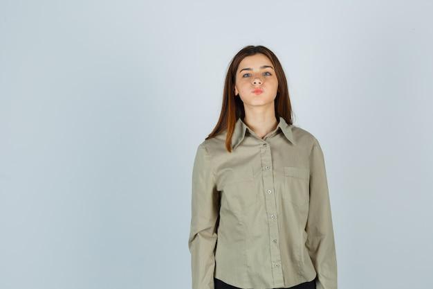 Giovane donna in camicia che soffia sulle guance, fa il broncio e sembra perplessa, vista frontale.