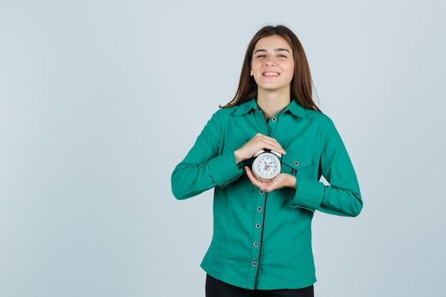 Young lady in shirt holding alarm clock and looking cheery , front view.