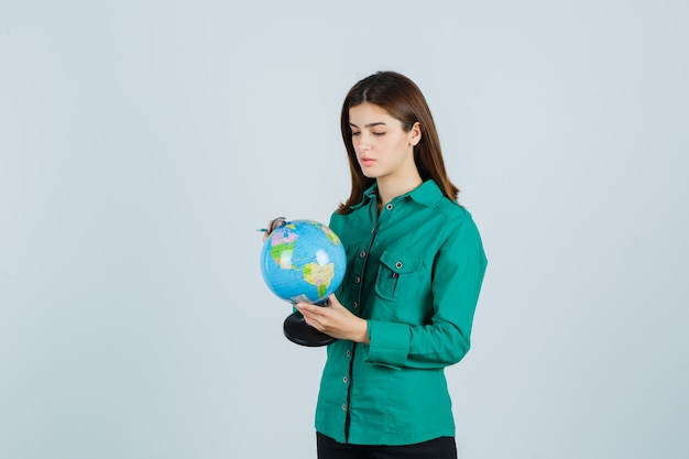 Young lady in shirt holding earth globe and looking careful , front view.
