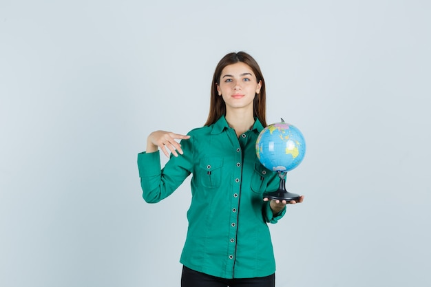 Young lady in shirt holding earth globe, pointing aside and looking pleased , front view.