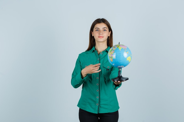 Young lady in shirt holding earth globe, pointing at it and looking confident , front view.