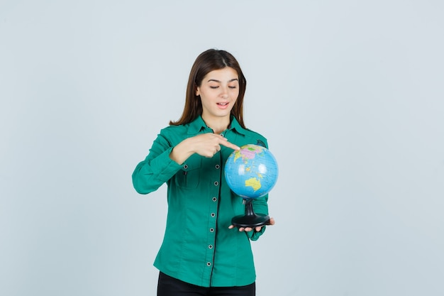 Young lady in shirt holding earth globe, pointing on it and looking excited , front view.