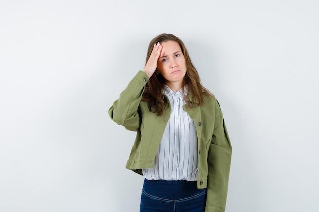 Giovane donna in camicia che tiene la mano sulla testa e sembra triste, vista frontale.