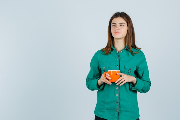 Young lady in shirt holding orange cup of tea and looking focused , front view.