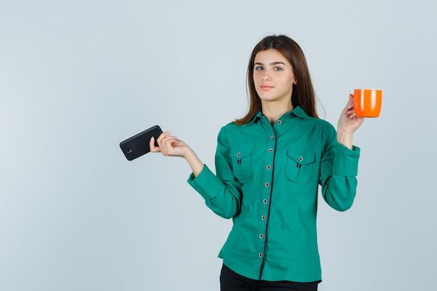 Giovane signora in camicia che tiene tazza arancione di tè e telefono cellulare e guardando fiducioso, vista frontale.