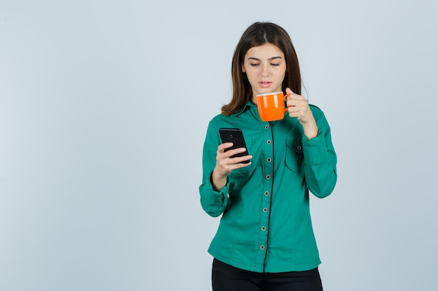 Young lady in shirt holding orange cup of tea and mobile phone and looking confident , front view.
