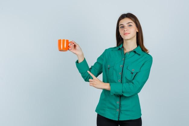 Giovane donna in camicia che tiene una tazza di tè arancione, indicando l'angolo in alto a sinistra e guardando fiducioso, vista frontale.