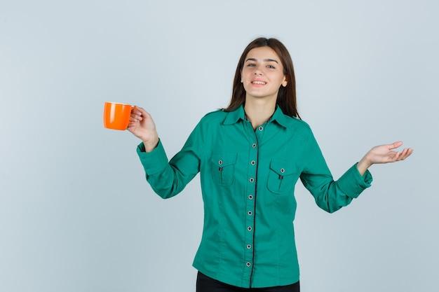 Giovane donna in camicia che tiene tazza di tè arancione, spalmando il palmo da parte e guardando allegro, vista frontale.
