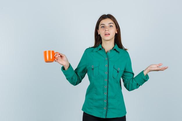 Giovane donna in camicia che tiene una tazza di tè arancione, spalmando il palmo da parte e guardando concentrato, vista frontale.