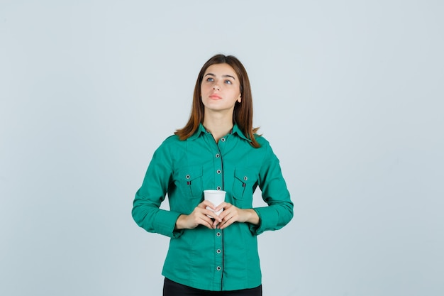 Young lady in shirt holding plastic cup of coffee and looking pensive , front view.