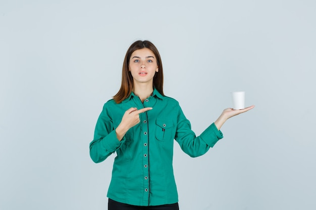Young lady in shirt holding plastic cup of coffee while pointing to the right side and looking focused , front view.