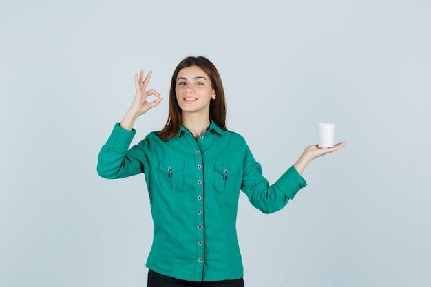 Giovane signora in camicia che tiene tazza di caffè di plastica mentre mostra il gesto giusto e sembra allegro, vista frontale.