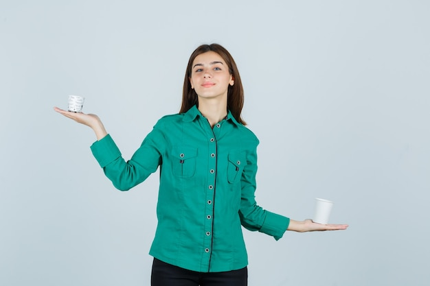 Young lady in shirt holding plastic cups of coffee and looking pleased , front view.
