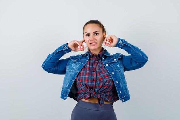 Giovane donna in camicia, giacca che tappa le orecchie con le dita e sembra turbata, vista frontale.