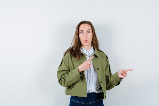 Giovane donna in camicia, giacca che punta da parte e sembra stupita, vista frontale.