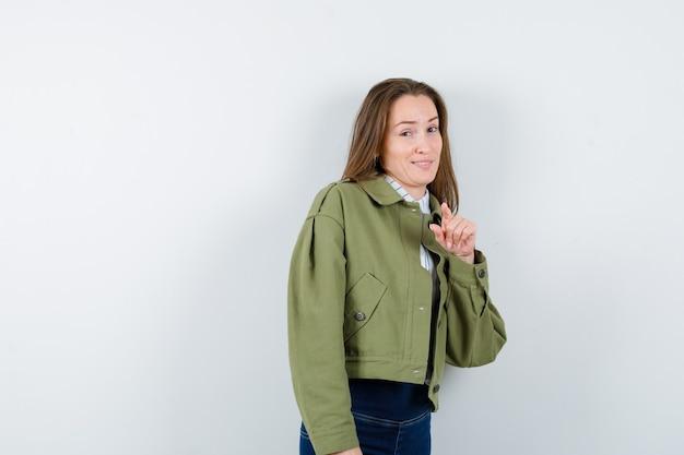 Giovane donna in camicia, giacca che punta alla telecamera e sembra felice, vista frontale.
