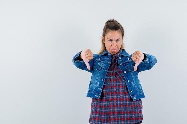 Giovane donna in camicia, giacca che mostra i doppi pollici verso il basso e sembra triste, vista frontale.