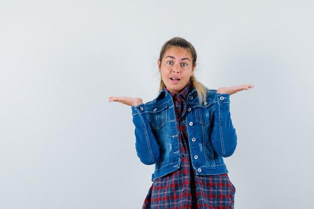 Giovane donna in camicia, giacca che mostra gesto impotente e che sembra confusa, vista frontale.