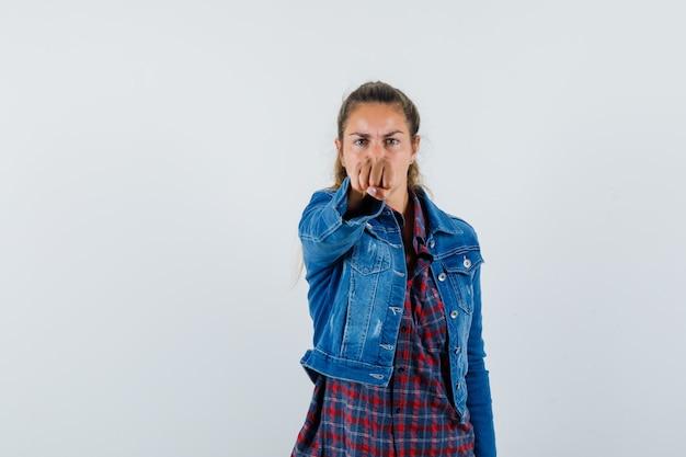 Giovane donna in camicia, giacca minacciosa con il pugno e sguardo dispettoso, vista frontale.