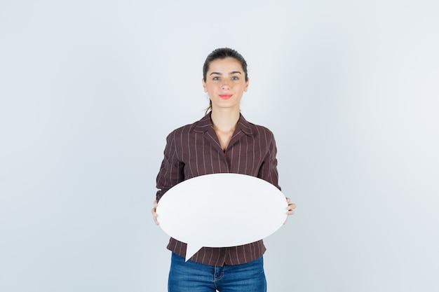 Giovane donna in camicia, jeans che tiene poster di carta e sembra carina, vista frontale.
