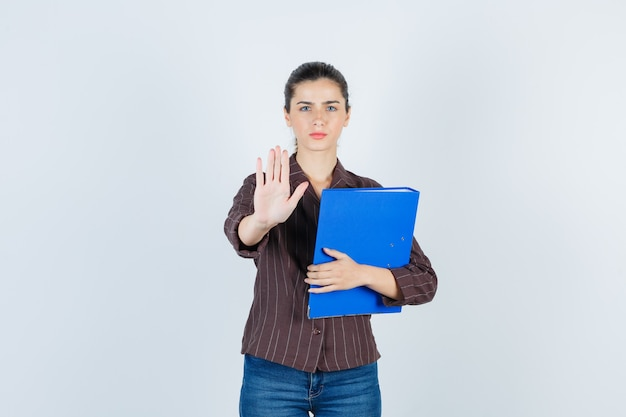 Young lady in shirt, jeans showing stop gesture, holding folder and looking serious , front view.