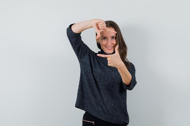 Giovane donna in camicia che fa il gesto del telaio e che sembra allegra