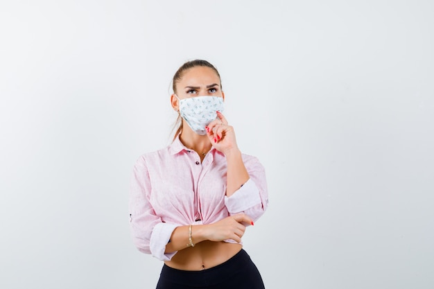 Young lady in shirt, mask keeping hand on chin and looking pensive , front view.