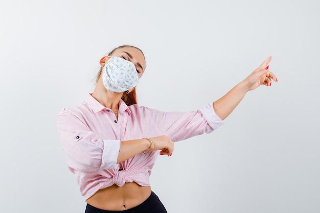 Giovane donna in camicia, maschera che punta all'angolo in alto a destra e sembra tranquilla, vista frontale