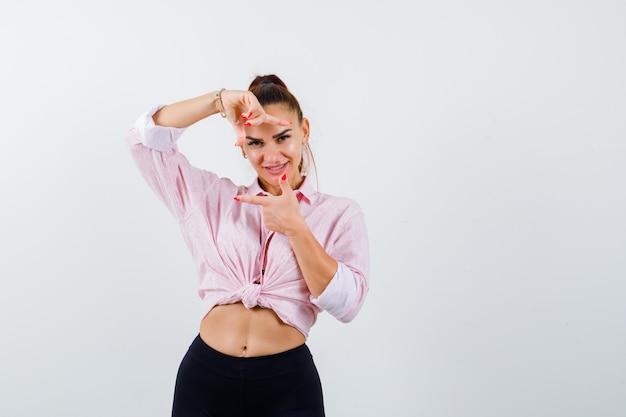 Giovane donna in camicia, pantaloni che fanno il gesto del telaio e che sembra allegra, vista frontale.