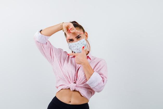 Giovane donna in camicia, pantaloni, maschera che fa il gesto del telaio e sembra allegra