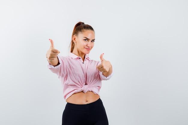 Giovane donna in camicia, pantaloni che mostra il doppio pollice in alto e sembra allegra, vista frontale.